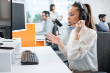 Young Dedicated Customer Support Representative Woman Talking With Client Using Hands-free Headset In Call Centre