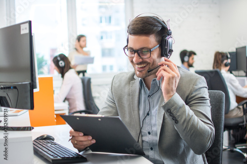 Fototapety, obrazy: Male technical support worker with headset reading something from clipboard while talking with a client in call center