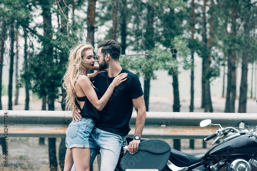 Canvastavla  young couple of bikers tenderly embracing near black motorcycle on road near gre
