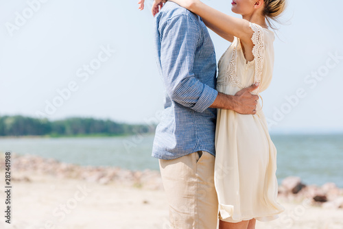 Canvas Prints Height scale cropped view of romantic couple hugging at beach