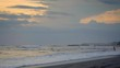 Slow motion of sunset beach with hig tide waves and people in ocean are swimming and surfing while kids are playing in water