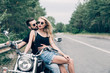 young couple of bikers closely sitting on black motorcycle on road near green forest