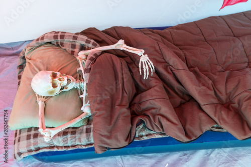 Fototapeta Skeleton relaxing in a tent while camping