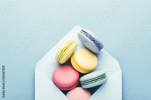 Poster Macarons Colorful macarons in envelope on blue background.