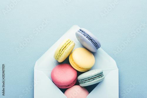 Foto auf AluDibond Macarons Colorful macarons in envelope on blue background.