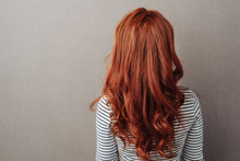 Rear View Of A Woman With Long Curly Red Hair