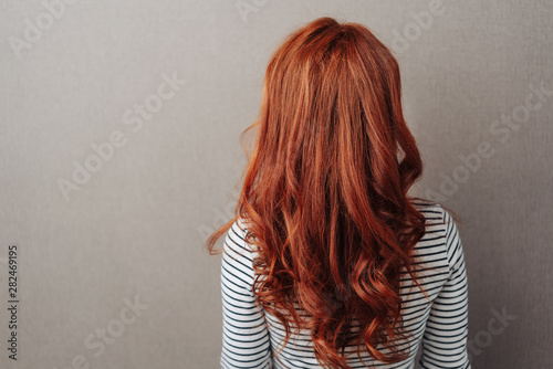 Fotomural Rear view of a woman with long curly red hair