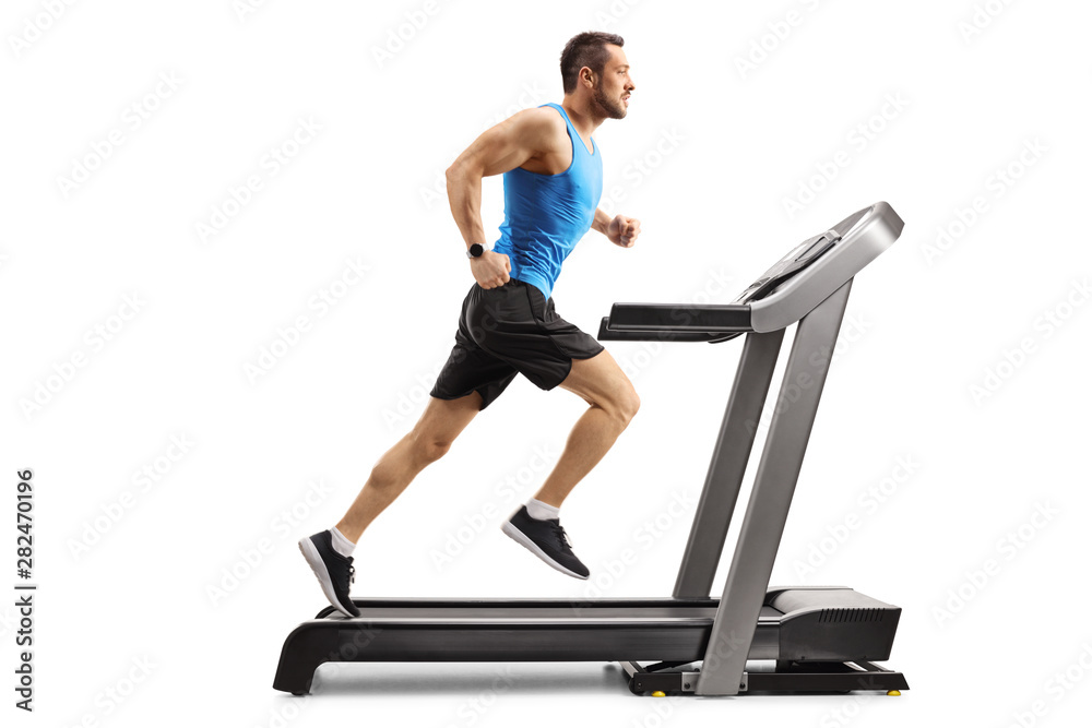 Fotografie, Obraz Young man in sportswear running on a professional treadmill