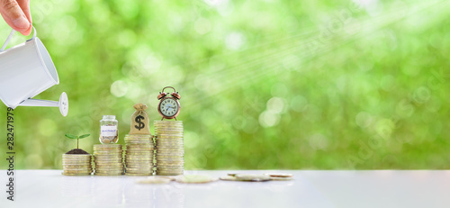 Photo Long-tern investment, time value of money concept : Clock, US dollar bag, glass jar, a small tree on steps of rising coins