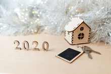 Concept For Business, New Year, Real Estate, Property, Rental, Hotel Business, Building. 2020 Happy New Year Wood Number, Wooden House And Keys On The Table