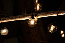 Warm Glowing Glass Light Bulbs Hanging From The Ceiling Of A Modern Restaurant