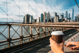 Fototapeta Nowy York - Detail of the hand of a girl holding a glass of coffee while watching New York from a bridge