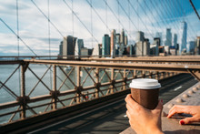 Detail Of The Hand Of A Girl Holding A Glass Of Coffee While Watching New York From A Bridge