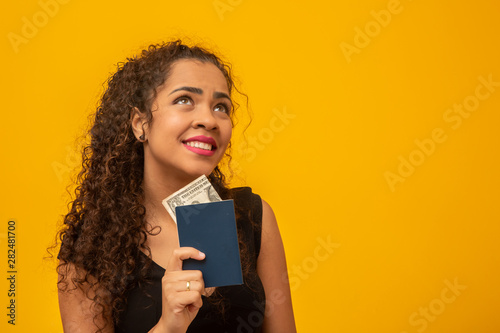 Fototapeta Beautiful young woman with curly hair holding a passport and money, thinking of her next trip. On yellow background obraz na płótnie