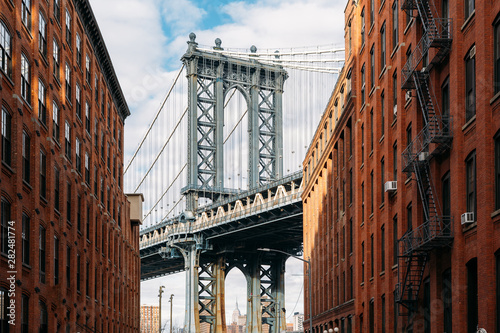 Brooklyn Bridge seen between two beautiful brown buildings at sunset - 282481774