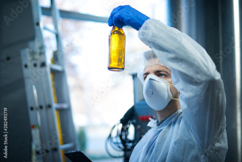 Technologist expert in beer production factory holding glass bottle and checking quality Fototapete