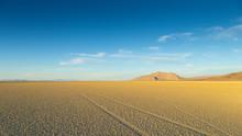 Vast Desert Playa At Black Rock Nevada At Sunset With Tire Tracks On Empty Cracked Mud.