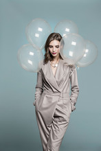 Portrait Of Female Fashion Model Standing With Balloons Against Blue Background