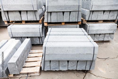 stockpiles of new gray concrete curbs