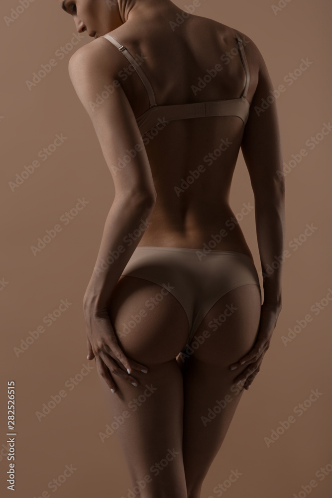 Fototapeta Skinny young woman in lingerie raises her buttocks with her hands - obraz na płótnie