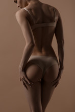Skinny Young Woman In Lingerie Raises Her Buttocks With Her Hands