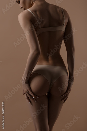 Obraz Skinny young woman in lingerie raises her buttocks with her hands - fototapety do salonu