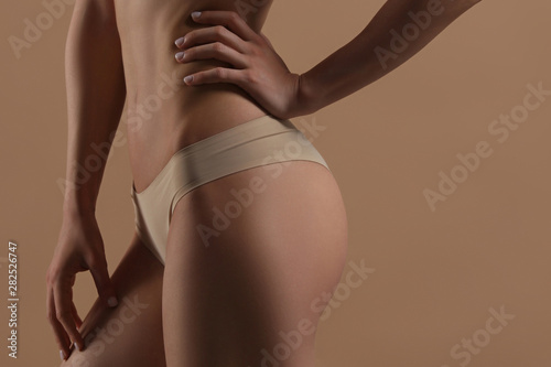 Thin young woman in underwear on beige background