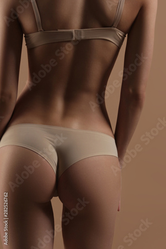Papiers peints Ane Thin young woman in underwear on beige background