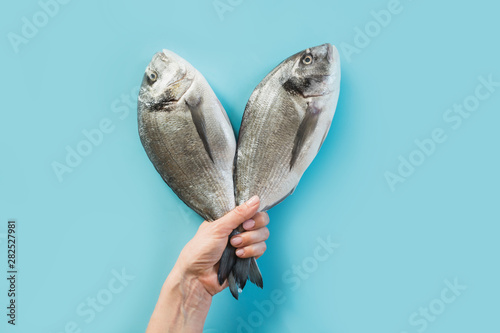 Fotografie, Obraz  Female hand with two dorado fish tail on blue paper as color of sea