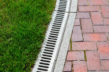 Iron Drainage System Between Paving Slabs And Green Lawn, Closeup Of An Iron Grille Along A Pedestrian Pavement.