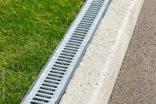 Fényképezés iron drainage system, closeup of an iron grille along a asphalt road and green grass