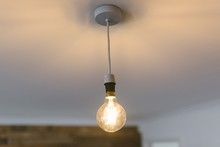 Closeup Shot Of A Large Illuminated Light Bulb Hanging From The Ceiling