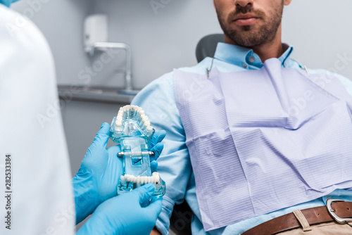 cropped view of woman in latex gloves holding teeth model near patient