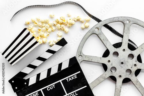 Filmmaker profession with clapperboard, popcorn and video tape on white backgrou Canvas-taulu