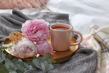 Tray With Cup Of Tea And Beautiful Bouquet On Bed
