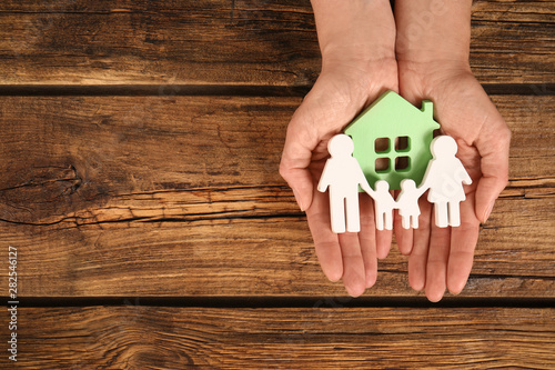 Fotografía Woman holding figures of family and green house in hands on wooden background, top view