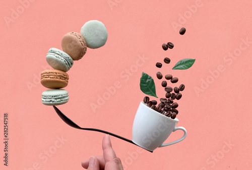 Aluminium Prints Macarons Balancing cup of coffee and macarons on a spoon on coral background