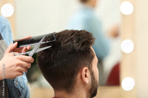 Barber making stylish haircut with professional scissors in beauty salon, closeu Wallpaper Mural
