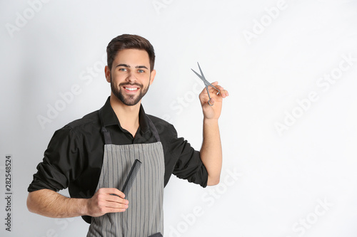 Young hairstylist holding professional scissors and comb on light background