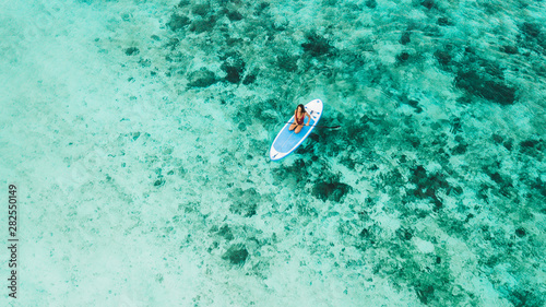 Foto Woman sitting on sup board and enjoying turquoise transparent water and coral reef