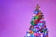 canvas print picture Christmas tree with multicolor led lights and purple copy-space background