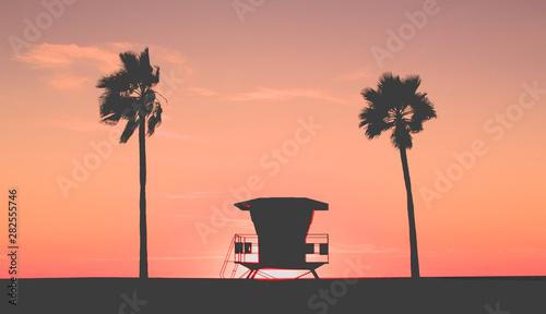 Beach Sunset with lifeguard tower, coastline and palm trees, USA.