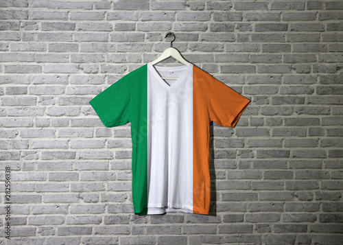 Ireland Flag On Shirt And Hanging On The Wall With Brick