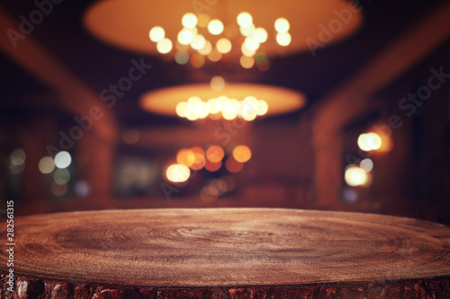 Fototapeta background Image of wooden table in front of abstract blurred restaurant lights obraz na płótnie