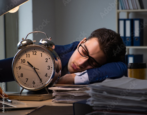 Valokuvatapetti Businessman falling asleep during long hours in office