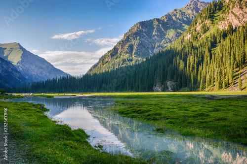 Photo  Idyllic summer landscape with hiking trail in the mountains with beautiful fresh green mountain pastures, river with reflection and forest