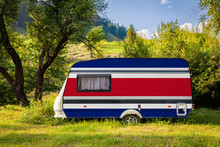 A Car Trailer, A Motor Home, Painted In The National Flag Of Costa Rica Stands Parked In A Mountainous. The Concept Of Road Transport, Trade, Export And Import Between Countries. Travel By Car