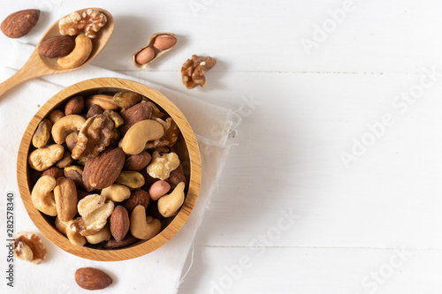 Top view of mixed nuts in a wooden bowl on white background - 282578340