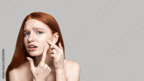 Skin problems. Worried young redhead woman examining her face while standing against grey background. Acne