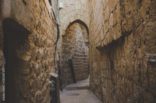 old city Jerusalem back street narrow alley with with arch passage between high stone and brick walls